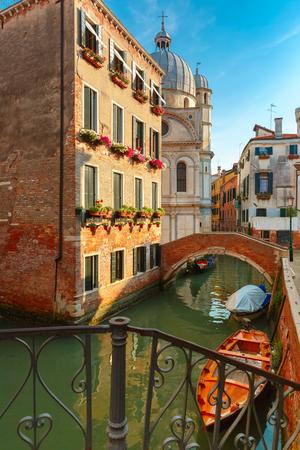 sestiere: Colorful narrow lateral canal, church Santa Maria dei Miracoli and pedestrian bridge in the sestiere of Cannaregio at morning, in Venice, Italia Stock Photo