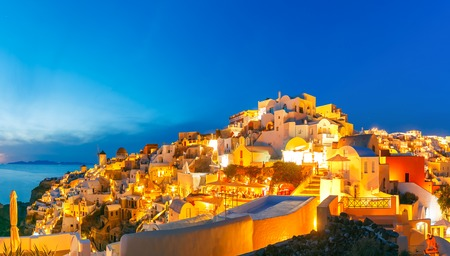 ia: Panoramic famous view, Old Town of Oia or Ia on the island Santorini, white houses and windmills at sunset, Greece