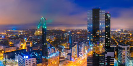 districts: Aerial panorama of modern business financial district with tall skyscraper buildings illuminated at night, Tallinn, Estonia