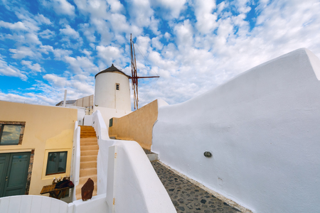 ia: White windmill and picturesque cloudy sky in Oia or Ia on the island Santorini, Greece