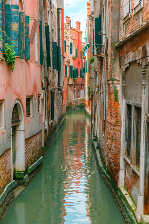 docked: Colorful narrow lateral canal in Venice with docked boat, Italy