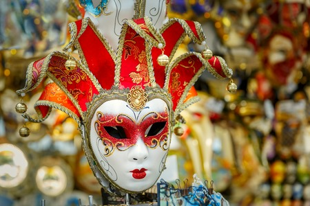 venice mask: Typical vintage venetian red and golden mask, symbol Annual carnival, in souvenir shop on a street of Venice, Veneto, Italy.
