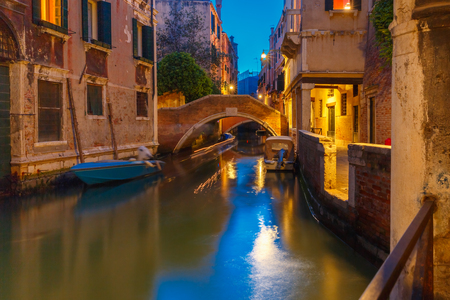venice bridge: Lateral canal and pedestrian bridge in Venice at night with street light illuminating bridge and houses, with docked boats, Italy