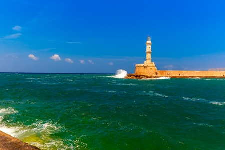 windstorm: Waves beat against the lighthouse in old harbour of Chania in the summer sunny day, Crete, Greece Stock Photo