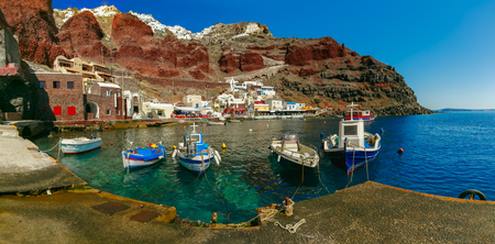 Panoramic view with fishing boats at Old port Amoudi of Oia village at Santorini island in Aegean sea, Greece Stock Photo