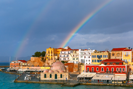 versicolor: Double rainbow in a cloudy sky above old harbour of Chania with Venetian quay and Kucuk Hasan Pasha Mosque in summer day, Crete, Greece Stock Photo
