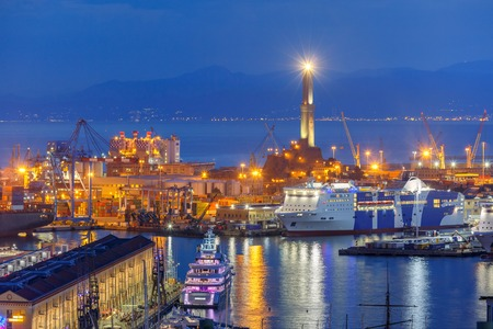 sea seaport: Historical Lanterna old Lighthouse, container and passenger terminals in seaport of Genoa on Mediterranean Sea, at night, Italy.