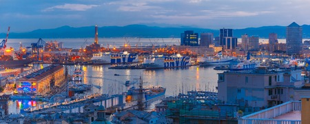 Panorama of Historical Lanterna old Lighthouse, container and passenger terminals in seaport of Genoa on Mediterranean Sea, at night, Italy. Stock Photo