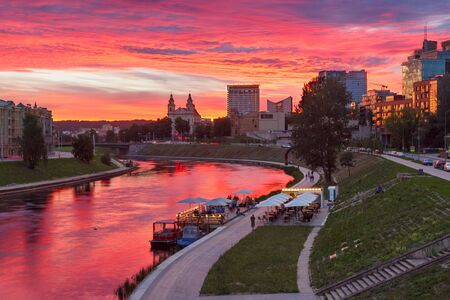 grandiose: Grandiose colorful sunset over Neris river, church and skyscrapers of New Center of Vilnius, Lithuania, Baltic states. Stock Photo