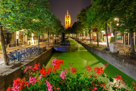 delft: Oude Delft canal and leaning tower of Gothic Protestant Oude Kerk church at night, Delft, Holland, Netherlands