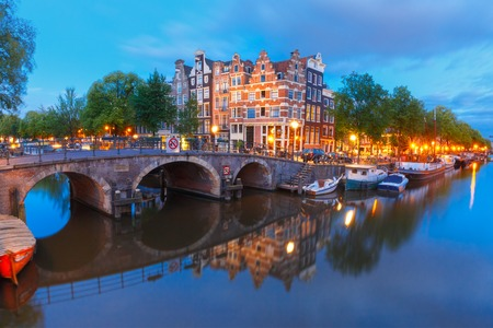 morning blue hour: Amsterdam canal, bridge and typical houses, boats and bicycles during morning twilight blue hour, Holland, Netherlands. Stock Photo