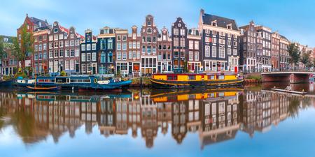 Panorama van de Amsterdamse gracht Singel met typische Nederlandse huizen en woonboten tijdens ochtend blauwe uur, Holland, Nederland. Stockfoto