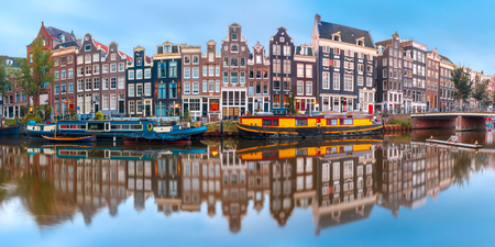 Panorama of Amsterdam canal Singel with typical dutch houses and houseboats during morning blue hour, Holland, Netherlands. Standard-Bild