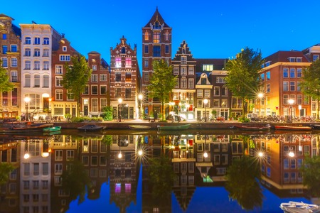 dutch typical: Night city view of Amsterdam canal Herengracht with typical dutch houses and their reflections, Holland, Netherlands.