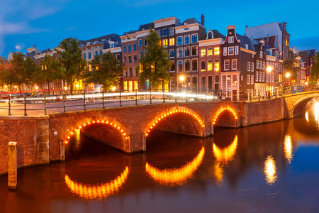 Amsterdam canal Reguliersgracht, bridge and typical houses, boats and bicycles during evening twilight blue hour, Holland, Netherlands. Stock Photo