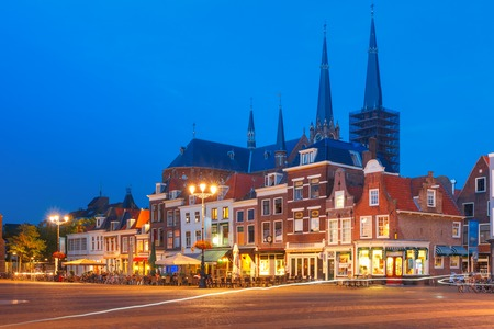 dutch typical: Typical Dutch houses on the Markt square in the center of the old city at night, and Maria van Jessekerk on the background, Delft, Holland, Netherlands