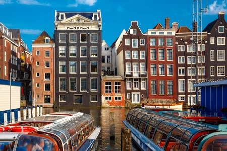 dutch typical: Beautiful typical Dutch dancing houses at the Amsterdam canal Damrak in sunny day, Holland, Netherlands. Stock Photo