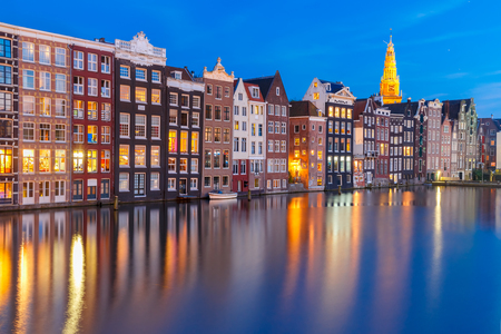 dutch typical: Amsterdam canal with Beautiful typical Dutch dancing houses and Oude Kerk church during twilight blue hour, Holland, Netherlands