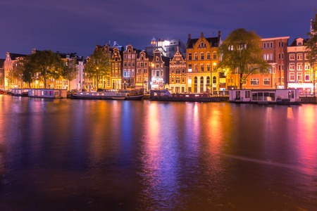 amstel: Amsterdam canal Amstel with typical dutch houses and houseboats with multi-colored reflections at night, Holland, Netherlands.