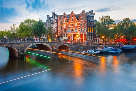morning blue hour: Amsterdam canal, bridge and typical houses, boats and luminous track from the boat during morning twilight blue hour, Holland, Netherlands.