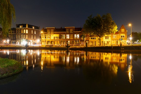 Night canal and typical dutch houses with their reflections in Delft, Holland, Netherlands Stock Photo