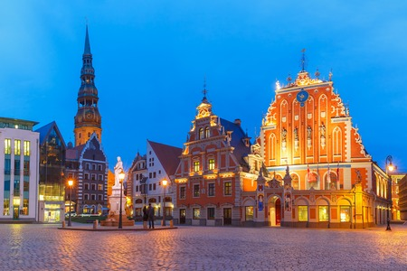 old town house: City Hall Square with House of the Blackheads and Saint Peter church in Old Town of Riga at night, Latvia Stock Photo