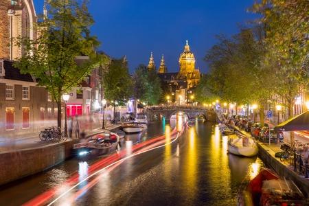 Night red-light district De Wallen, canal, Basilica of Saint Nicholas and bridge, Amsterdam, Holland, Netherlands. Long exposure.