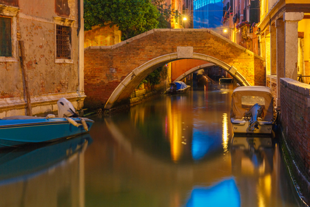 docked: Lateral canal and pedestrian bridge in Venice at night with street light illuminating bridge and houses, with docked boats, Italy