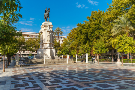 Overview of the New Square, Plaza Nueva, with the monument to King Ferdinand III in the center, in the sunny summer day, Seville, Andalusia, Spain Stock Photo