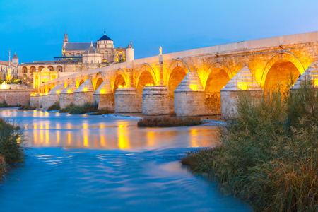 Illuminated Great Mosque Mezquita - Catedral de Cordoba with mirror reflection and Roman bridge across Guadalquivir river during morning blue hour, Cordoba, Andalusia, Spain Stock Photo