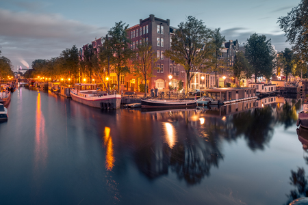 Amsterdam canals and typical houses, boats and bicycles during evening twilight blue hour, Holland, Netherlands. Stock Photo