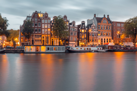 amstel: Amsterdam canal Amstel with typical dutch houses and boats during twilight blue hour, Holland, Netherlands. Stock Photo