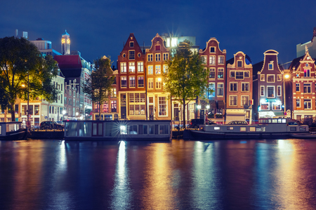 amstel: Amsterdam canal Amstel with typical dutch houses and houseboats with multi-colored reflections at night, Holland, Netherlands. Used toning Stock Photo