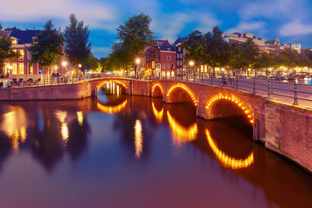 Amsterdam canal, bridge and typical houses, boats and bicycles during evening twilight blue hour, Holland, Netherlands. Used toning Stock Photo
