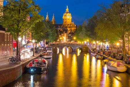 house gables: Night red-light district De Wallen, canal, Basilica of Saint Nicholas and bridge, Amsterdam, Holland, Netherlands. Long exposure.