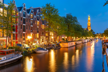 Night city view of Amsterdam canal Prinsengracht with houseboats and Westerkerk church, Holland, Netherlands. Stock Photo