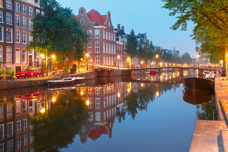 Amsterdam canal Kloveniersburgwal with typical dutch houses, bridge and houseboats during morning blue hour, Holland, Netherlands. Stock Photo