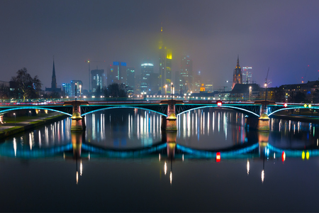 reflection: Picturesque view of Frankfurt am Main skyline and Ignatz Bubis Brucke bridge during evening blue hour with mirror reflections in the river, Germany Stock Photo