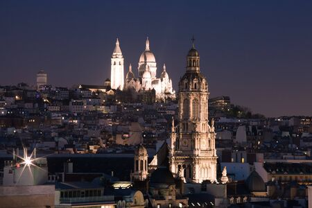 illuminated: Aerial view of Sacre-Coeur Basilica or Basilica of the Sacred Heart of Jesus at the butte Montmartre and Saint Trinity church at night, Paris, France