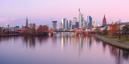 Picturesque panoramic view of business district with skyscrapers and mirror reflections in the river at sunrise, Frankfurt am Main, Germany