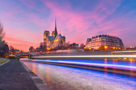 grandiose: Picturesque grandiose sunset over Cathedral of Notre Dame de Paris and luminous track from the boat, France