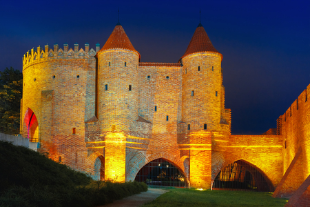 semicircular: Semicircular fortified medieval outpost Barbican in the Old Town of Warsaw at night, Poland