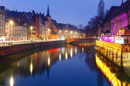 saint nicolas: Picturesque quay and church of Saint Nicolas with mirror reflections in the river Ile and Christmas garland during morning blue hour, Strasbourg, Alsace, France