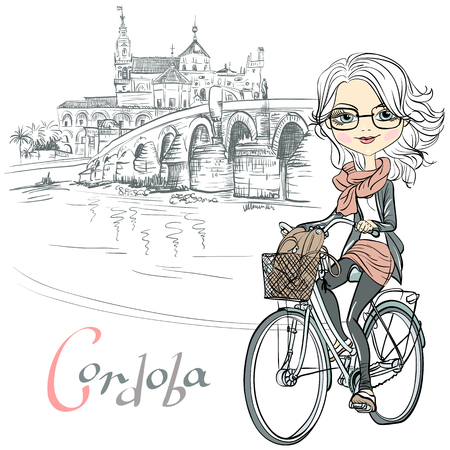 Cute beautiful fashionable girl rides a bike in Cordoba, Andalusia, Spain. Mosque Mezquita and Roman bridge on the background