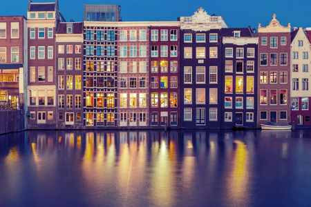 illuminating: Beautiful typical Dutch dancing houses at the Amsterdam canal Damrak at night, Holland, Netherlands.