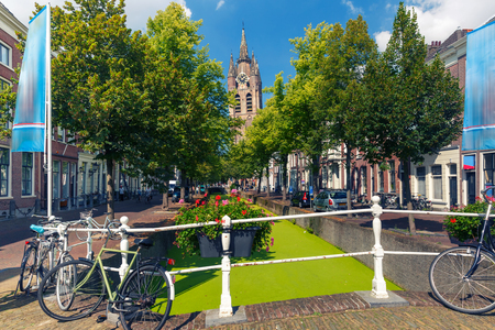The picturesque Oude Delft canal and leaning tower of Gothic Protestant Oude Kerk church on a sunny day in Delft, South Holland, Netherlands. Stock Photo