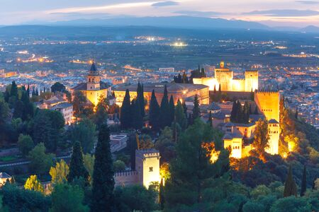 Palace and fortress complex Alhambra with Iglesia de Santa Maria, Palacios Nazaries and Alcazaba during evening blue hour in Granada, Andalusia, Spain