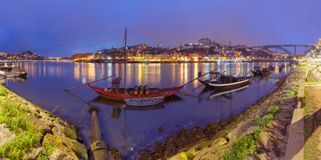 rabelo: Panoramic view, traditional rabelo boats with barrels of Port wine on the Douro river, Ribeira and Dom Luis I or Luiz I iron bridge on the background, Porto, Portugal.