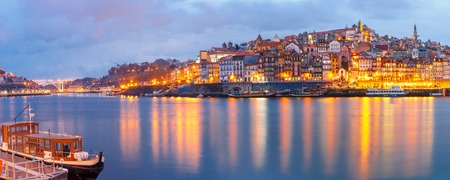 river banks: Ribeira and Old town of Porto with mirror reflections in the Douro River during evening blue hour, Portugal, Portugal.