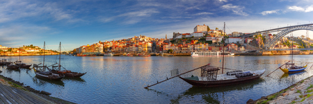 rabelo: Panoramic view of traditional rabelo boats with barrels of Port wine on the Douro river, Ribeira and Dom Luis I or Luiz I iron bridge on the background, Porto, Portugal.